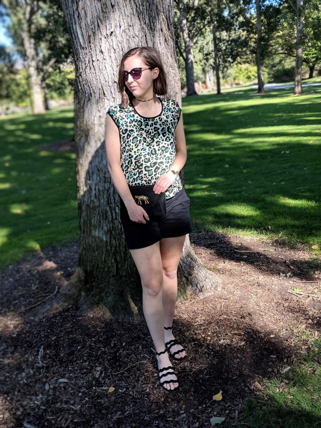 green leopard blouse, black shorts, black sandals