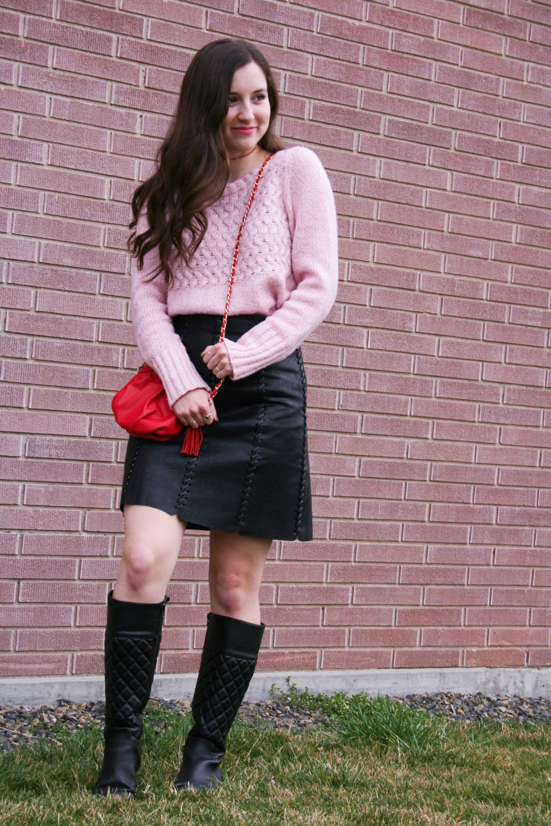pink sweater, red purse, black pleather skirt, black boots