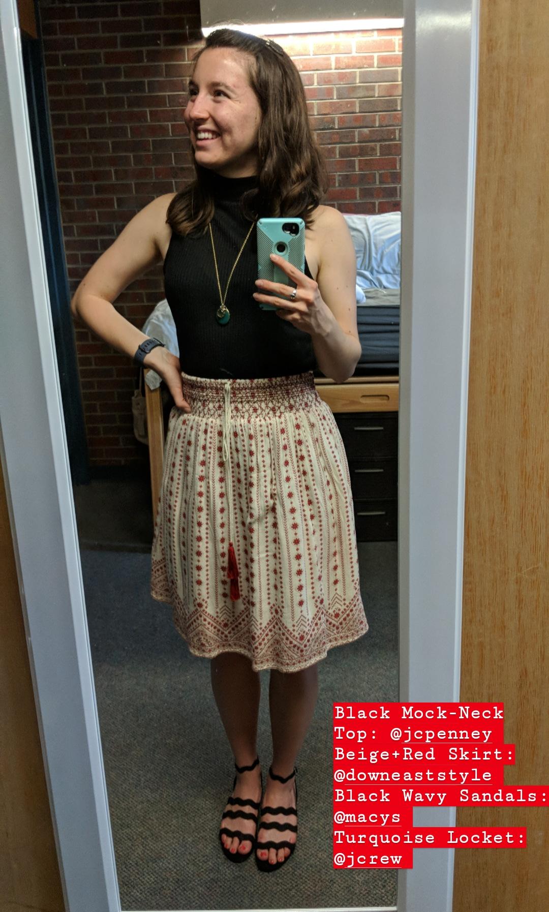 black mockneck top, red patterned skirt, black wavy sandals