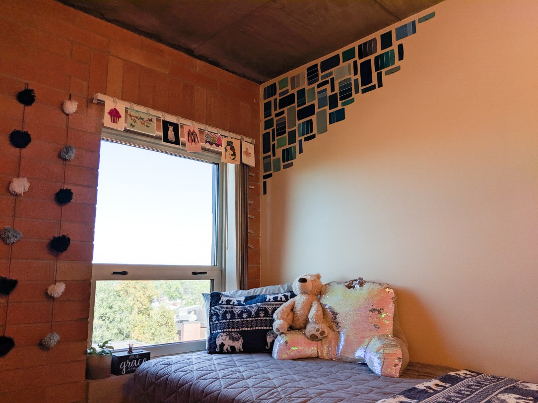 college dorm room, paint chip mural, string lights, pom pom garland