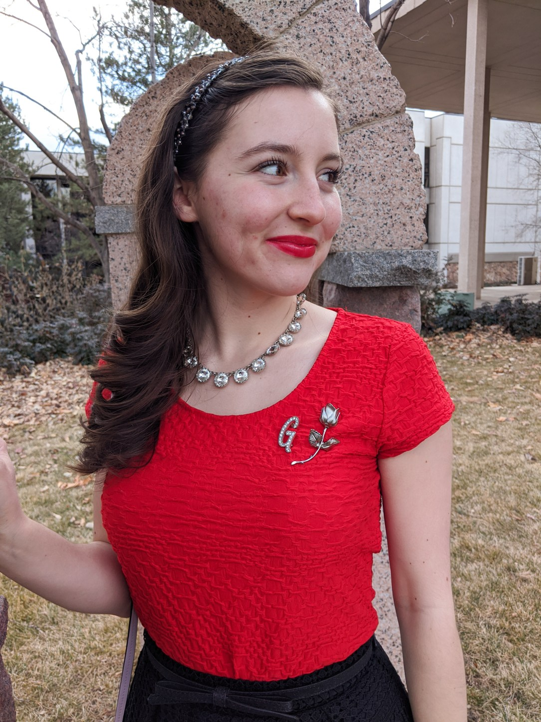 crystal statement necklace, red blouse, brooches, rose pin, red lipstick