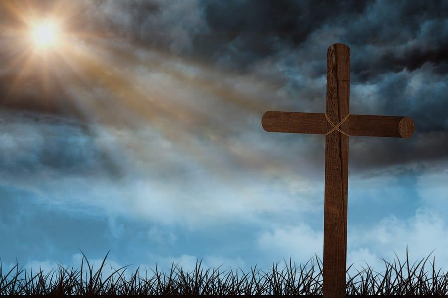 Wooden cross with sun shining through dark clouds.