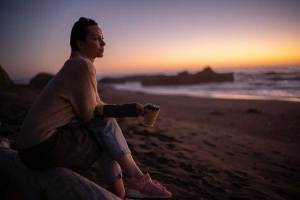 Pensive woman on beach at sunset.