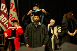 Graduate student being hooded at commencement ceremony.