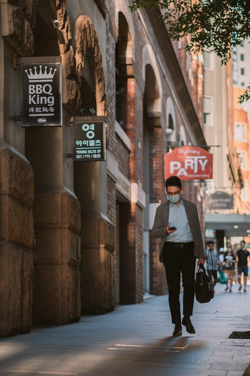 man texting while walking on sidewalk