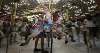 A little girl waves to a crowd of people while on a carousel on Saturday, October 7, 2017, at the Georgia National Fair in Perry, Georgia. (Photo/Mary Grace Heath)