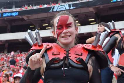 """Abbey Swearngin, 18, a genetics major, at the University of Georgia, participates as a member of the Spike Squad during the Georgia vs. Tennessee football game at Sanford Stadium, on September 29, 2018. Sitting field-level at Sanford Stadium, Swearngin dons themed red paint that mimics David Bowie's famous lightning bolt symbol. Swearngin says that she joined the Spike Squad to make new friends and that """"it's the best way to spend a football game!"""""""