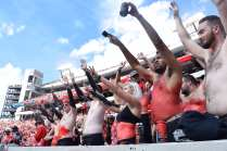 Members of the Spike Squad, a University of Georgia student group that wears paint and costumes to cheer on the Georgia Bulldogs football team, raise their arms to celebrate the team coming onto the field during the Georgia vs. Tennessee football game on September 29, 2018. The Spike Squad sits on the front row of the student section and pumps their arms up and down in a celebratory manner.