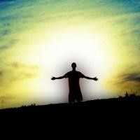 Człowiek mężczyzna chłopak na wzgórzu na tle zachodzącego słońca