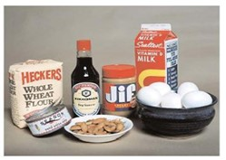 image of 8 common allergens: wheat (bag of flour), soy (bottle of soy sauce), milk (carton of milk), peanut butter (jar of Jif), eggs (bowl of eggs), fish (can of tuna), shellfish (bowl of cooked shrimp)