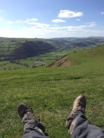 feet in forefront of green hills