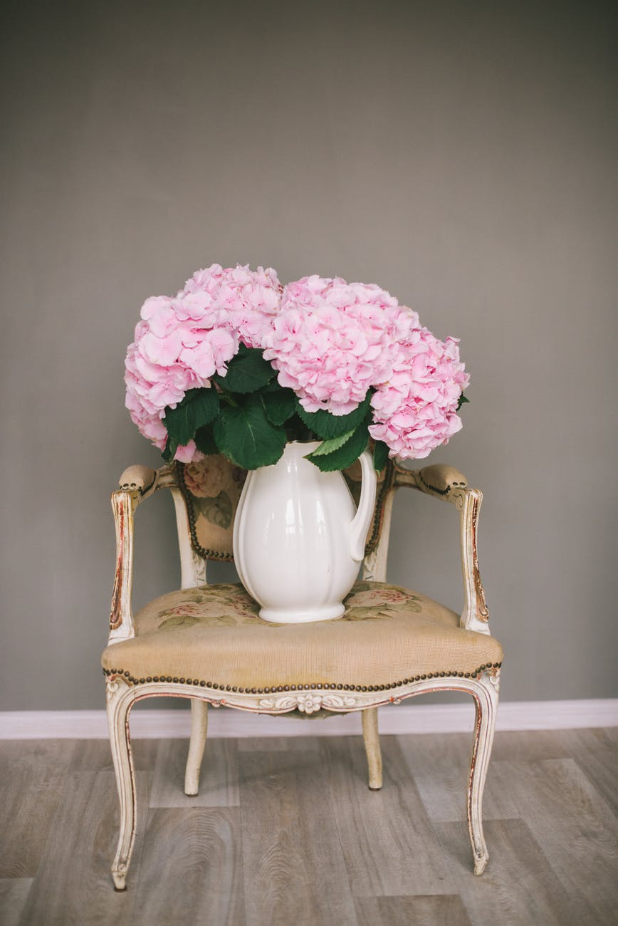 white ceramic vase with pink flowers on white wooden table