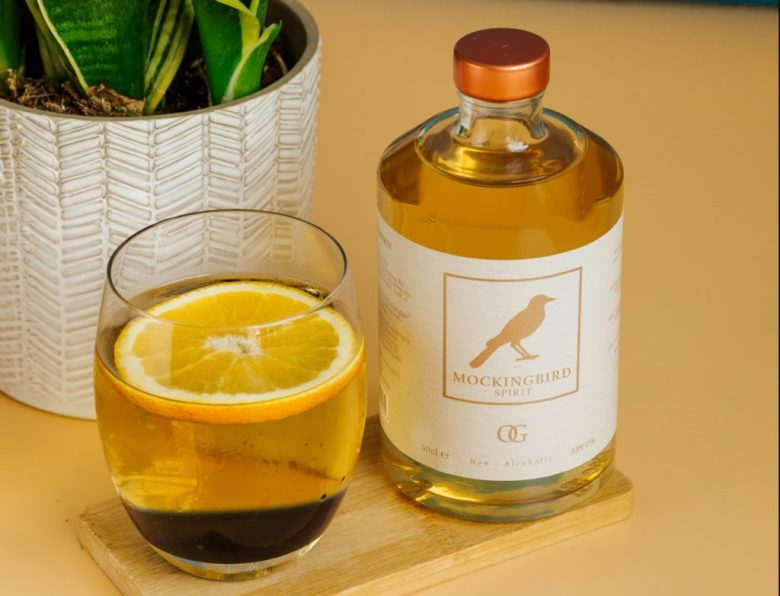 A small glass of Mockingbird Spirit next to a bottle.