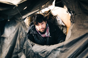 An Afghani man looks out through a hole in his tent. The vast majority of Jungle residents are males of fighting age, who in many cases were forced to leave because they refused to fight in their home countries. 27th Feb