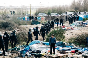 Riot police finish their shift and go home on the day demolition of the southern part of the Calais jungle started - 1st March.