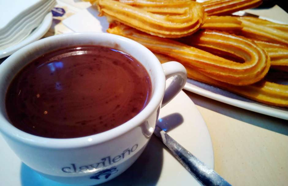 A plate of sugared churros and a cup of rich hot chocolate