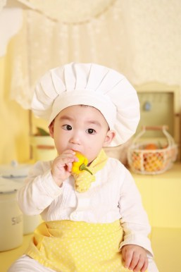 bébé cuisinier qui mange un poivron