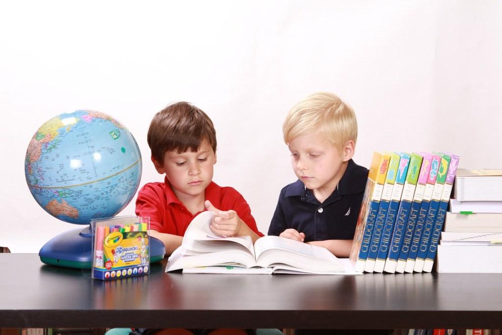 deux enfants qui lisent une encyclopédie