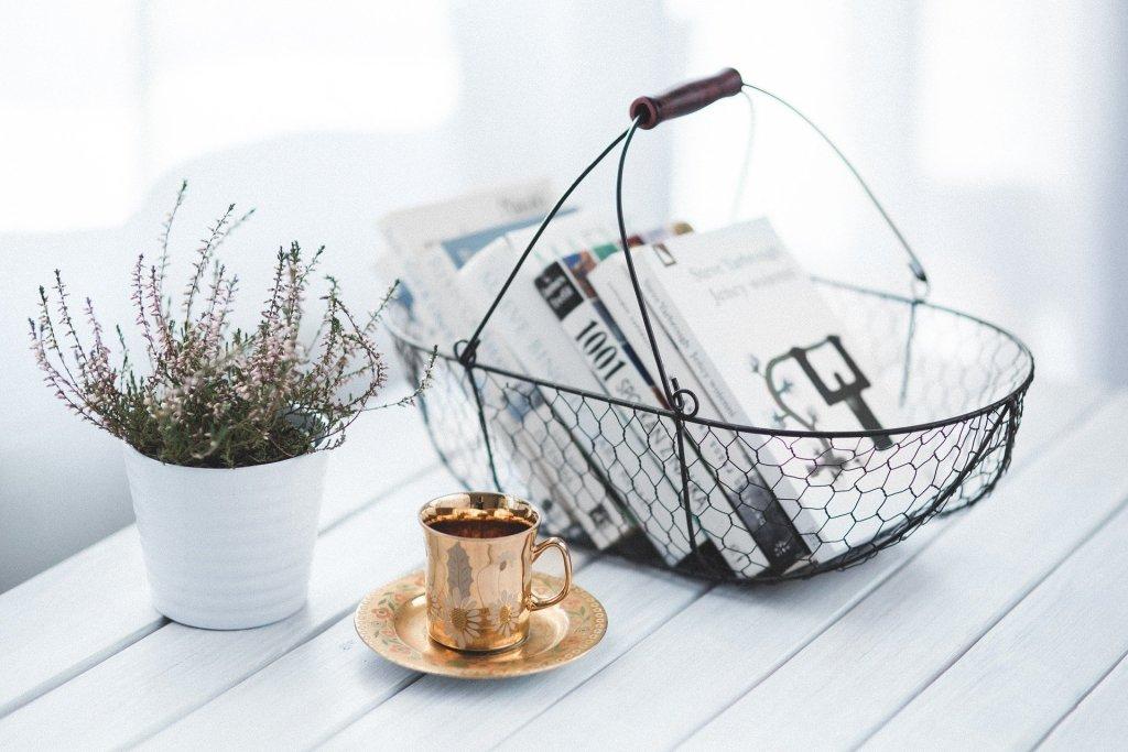 Des livres dans un panier posés sur une table accompagné d'une plante et d'une tasse de café
