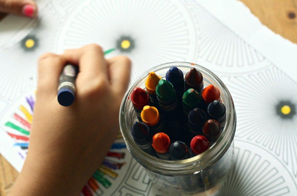 main d'enfant qui fait un coloriage