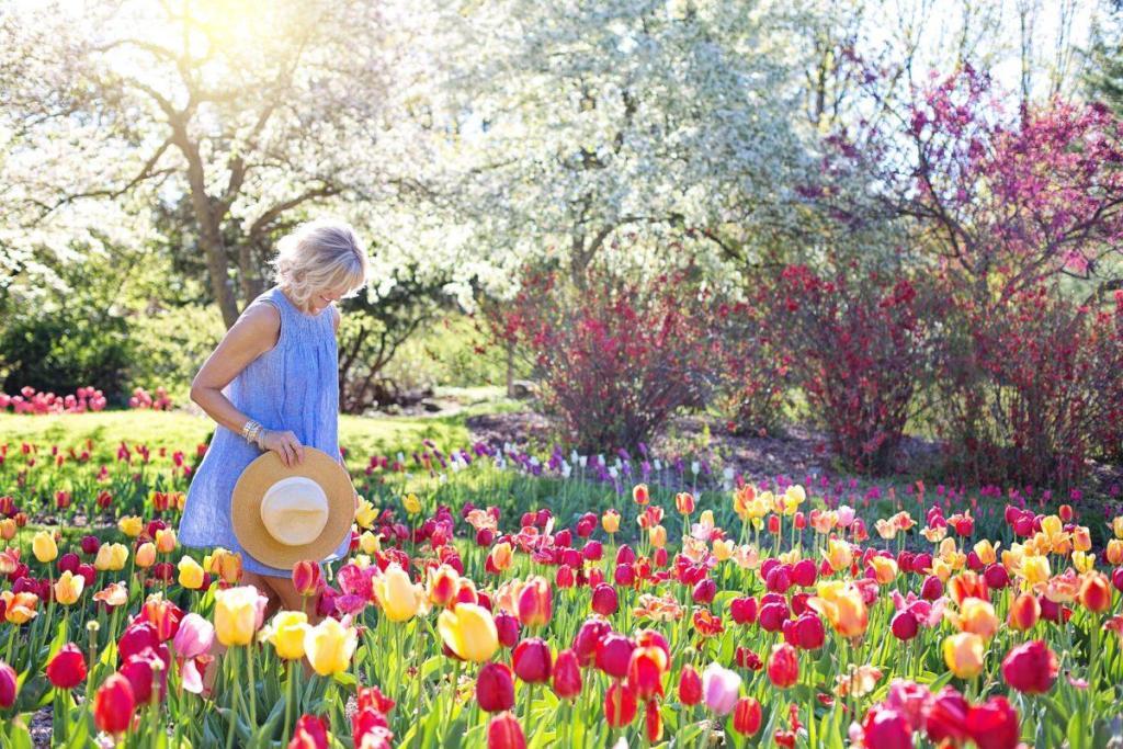Une femme blonde au milieu d'un jardin de tulipe