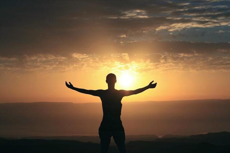 Homme les bras écarté vers le soleil en train d'utiliser la loi d'attraction