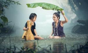 Une enfant et un adulte s'amusant sous une pluie de mousson