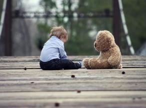 Petit garçon sur un pont avec un ours en peluche