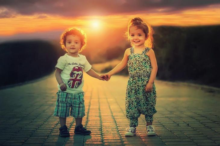 Des enfants se tenant la main avec un coucher de soleil
