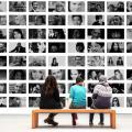 Des personnes assises sur un banc devant un mur de photos