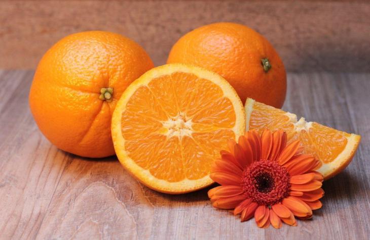 Des oranges sur une table avec une fleur orange