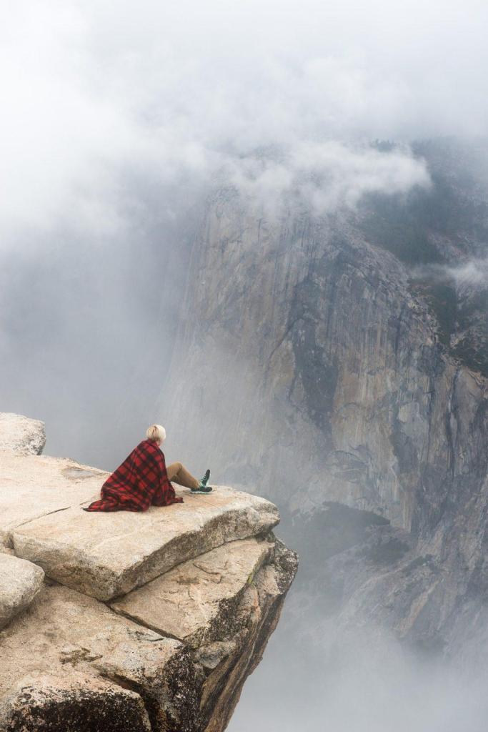Un homme seul sur le bord d'un rocher en montagne