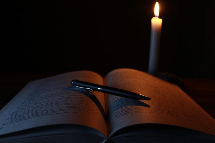 Un livre ouvert avec une bougie et un crayon