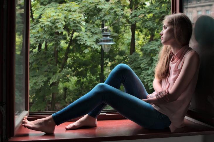 Une femme observant par la fenêtre