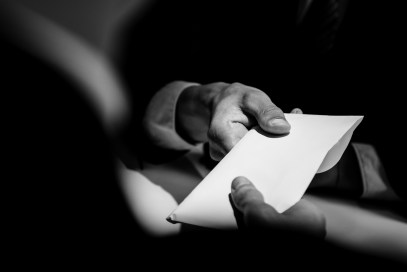 Businessman giving bribe money in the envelope to partner