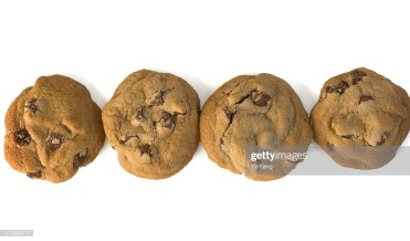Subject: A row of four chocolate chip cookies on a white background