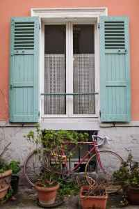 window with green shutters on peach colored house in paris