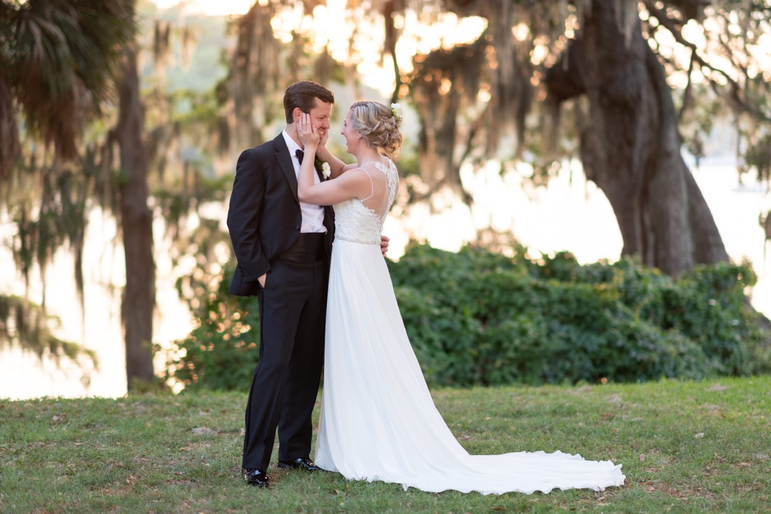 Bride pulling groom in for a kiss with her hands on his cheeks  - Wachesaw Plantation