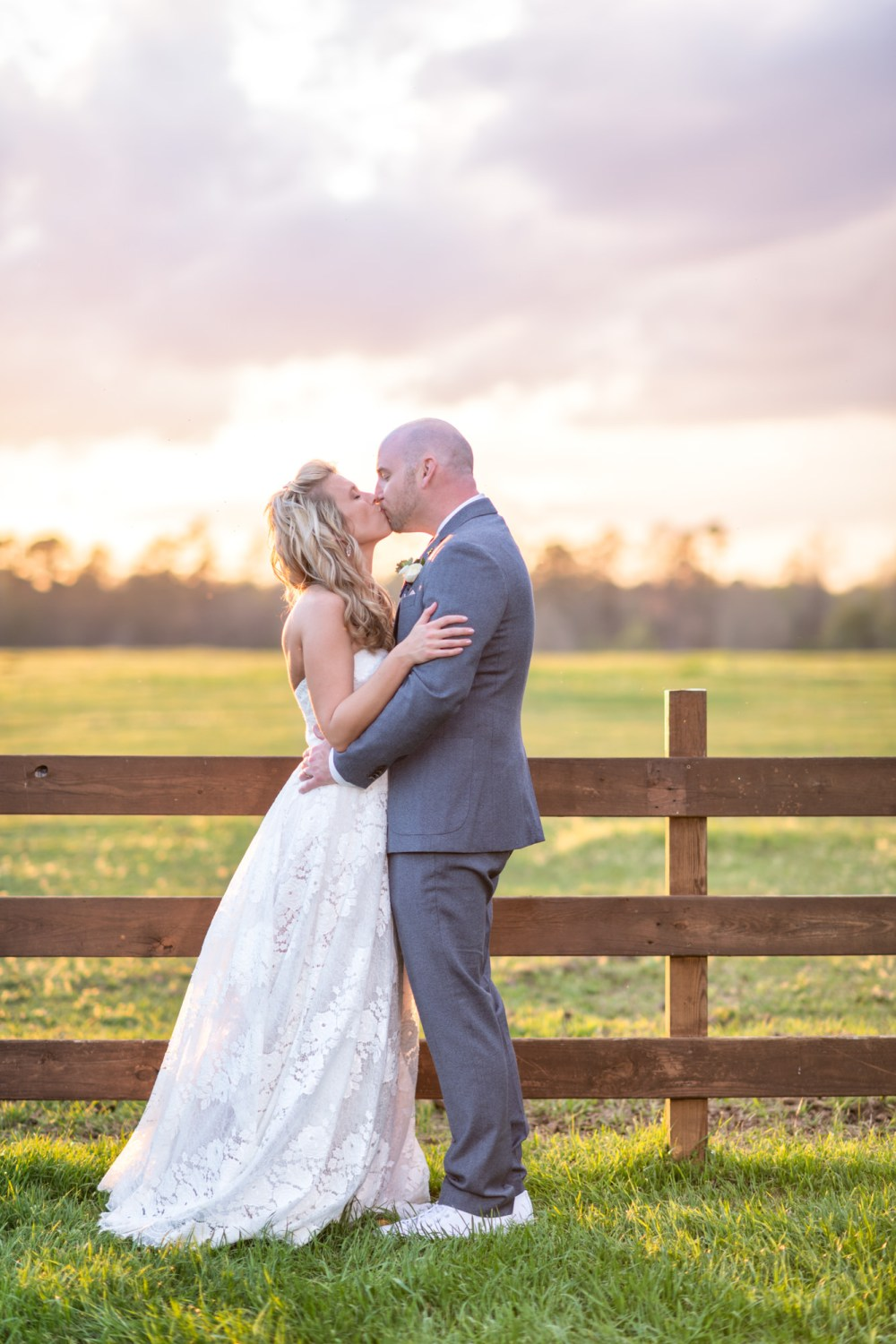 Groom pulling bride in for a kiss at sunset - Wildhorse at Parker Farms