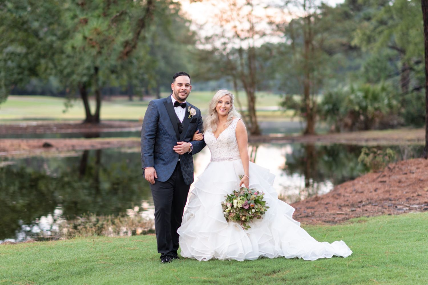 Portraits of the bride and groom in front of the golf course lake - Litchfield Country Club