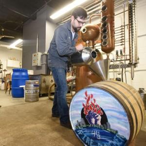 Spencer pours vodka into a barrel