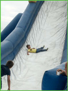 Young Boy Coming Down Slide Sideways