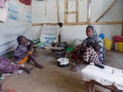S and her children waiting for food in the camp