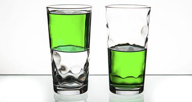 Two glasses, both half-full of green liquid.