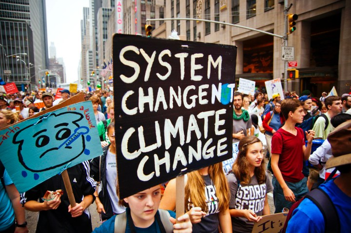 "Climate march with people holding a sign saying ""System Change Not Climate Change"""