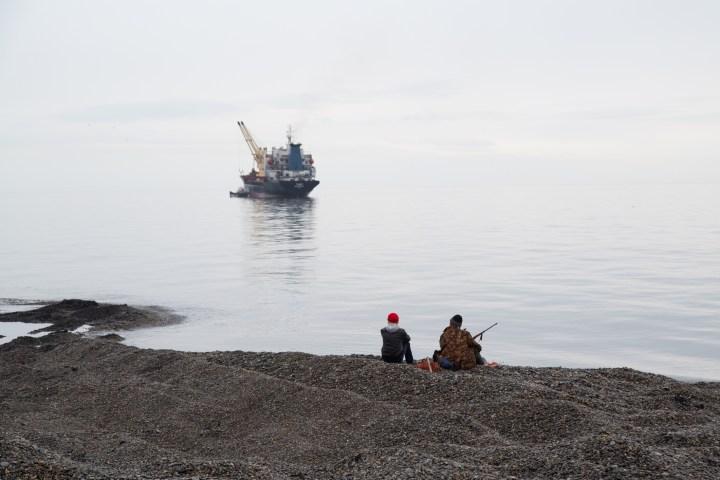 Hunters look at the ship in Uelen, Chukotski region, Russia