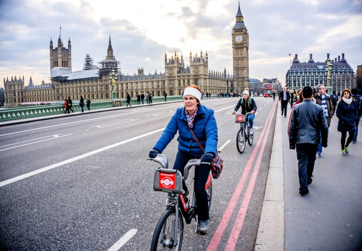 Cyclists crossing Westminster Bridge in London with  Big Ben and the Houses of Parliament behind. People are walking on the pavement