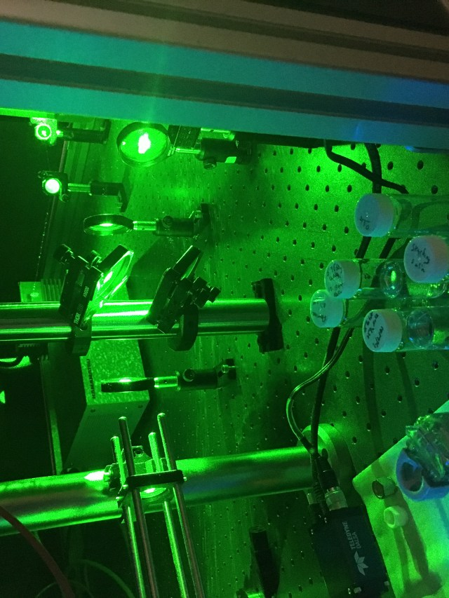 Image inside Lara's lab. There are green lasers being reflected by mirrors and a number of plastic test tubes containing colourless liquid in the foreground.