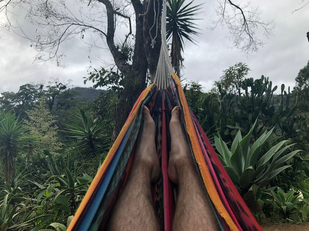 photo taken from hammock of my dirty legs in contrast to my pale white feet, with a rich hillside nature in the background.