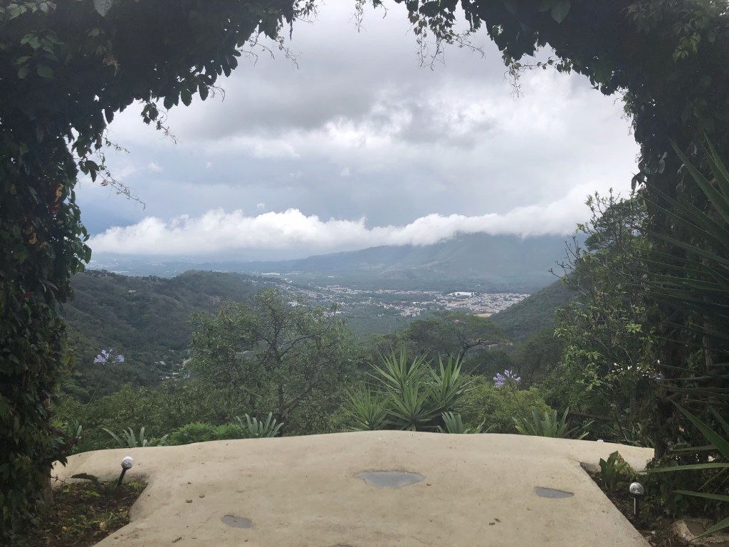 Photo taken through a shrub-covered arch towards the Antigua valley.